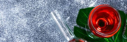 Wine in a wineglass, a bottle and a tropical leaf. Top view. Wine drink on a gray background. Copy space.  royalty free stock image