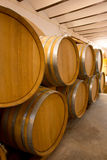 Wine wooden oak barrels stacked in a row at winery Stock Photos