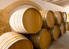 Wine wooden oak barrels stacked in a row at winery Royalty Free Stock Photos