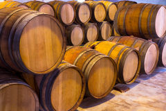 Wine wooden oak barrels stacked in a row at winery Royalty Free Stock Images