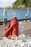 Wine on a yacht. A bottle of wine on the wooden deck of a yacht Stock Image