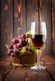 Wineexponeringsglas och druvor i en korg Arkivfoton
