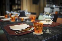 Wineexponeringsglas och plattor på tabellen Royaltyfri Bild