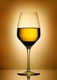 Wineexponeringsglas över guld- bakgrund Arkivfoton