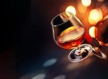 Wineglass κονιάκ με το ζωηρόχρωμο εορταστικό φωτισμό στο μαύρο υπόβαθρο στοκ φωτογραφία
