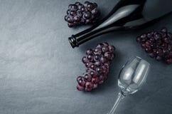Wineglass, μπουκάλι και ώριμα σταφύλια στο μαύρο υπόβαθρο πετρών Στοκ Εικόνες
