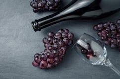 Wineglass, μπουκάλι και ώριμα σταφύλια στο μαύρο υπόβαθρο πετρών Στοκ φωτογραφία με δικαίωμα ελεύθερης χρήσης