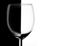 Wineglass. Transparent wineglass over contrast black and white background royalty free stock images