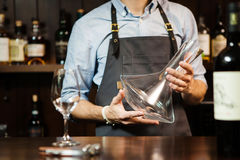 Wineglass at barcounter at background of sommelier with emty decanter. Wineglass at bar counter at background of sommelier with emty decanter. Glass carafe Stock Photos