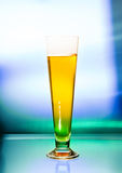 Wineglass of beer. A glass of beer with a colored background behind Stock Photos
