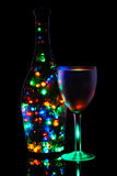 A wineglass and a bottle of lighted garland. Festive illuminations Stock Photos