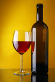 Wineglass and bottle of red wine Stock Image
