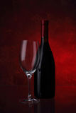 Wineglass and bottle with red wine. On red background Stock Photography