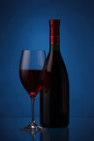 Wineglass and bottle with red wine. Wineglass and bottle of red wine on blue background Stock Photos