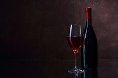 Wineglass and bottle with red wine. On brown background Stock Photography
