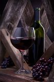 Wineglass and bottle in a rustic wine cellar setting. Red wine in glass with bottle and grapes in a rustic wood setting or wine cellar royalty free stock photos
