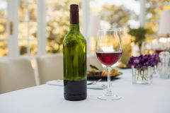 Wineglass and bottle on table in restaurant Stock Images