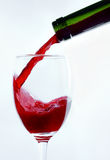 Wineglass, bottle, wine is flowing Royalty Free Stock Photos