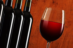 Wineglass and bottles of red wine Royalty Free Stock Photos