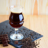 Wineglass of chocolate beer serving on black rock with chocolate and barley. Beverage background with a copy space. Wineglass of chocolate beer serving on black stock photos