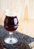 Wineglass of chocolate beer serving on black rock with chocolate and barley. Vertical beverage background with a copy space. Wineglass of chocolate beer serving stock photo