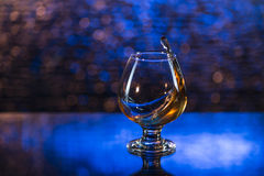 Wineglass of cognac and splash on a blue bokeh background Stock Image