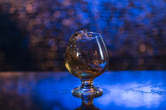 Wineglass of cognac and splash on a blue bokeh background Royalty Free Stock Photo