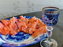 Wineglass of cold vodka and sliced salmon on a plate Gzhel. Natural food, appetizer. Gorgeous home appetizer. Under a glass of vodka.Gzhel - Russian folk craft royalty free stock photography