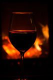Wineglass by a cozy fire. Wineglass with red wine in front of a glowing fire Stock Photos
