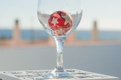Wineglass with decoration ball. Wineglass with red decoration ball & x28;outdoor& x29 Royalty Free Stock Photography