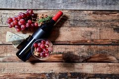 Wineglass filled with ripe grapes on table with fragrant blue cheese and bread with wine bottle.  stock photos