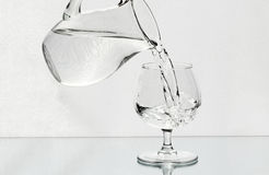 Wineglass is filled with a water from a jug Royalty Free Stock Images