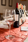 Wineglass in Front of Row of Wine Bottles on Velvet Royalty Free Stock Photography