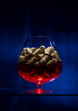Wineglass is on the glass table. You can see a glass with a lot of corks inside. It is standing on the glass table. The background is blue.  And the bottom of Stock Photo