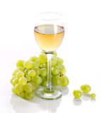 Wineglass with grapevine and green bunch grape Stock Photo