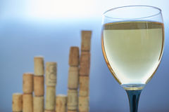 Wineglass with graph chart made from corks. Wineglass of white wine with blurred graph chart made from wine corks. for wine making industry business as Royalty Free Stock Photography