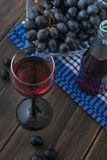 A wineglass of Italian Chianti young red wine with a bunch of gr. Apes on black wooden rustic table close-up Royalty Free Stock Image