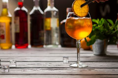 Wineglass with orange drink. Tongs hold slice of orange. Aperol spritz served at bar. Soda water and sparkling wine Stock Image