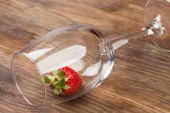 Wineglass with red ripe strawberry inside. Clean empty wineglass with red ripe strawberry inside, wooden background Stock Images
