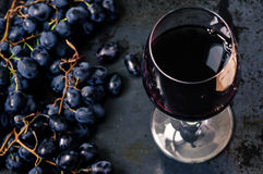 Wineglass of red wine with grapes Royalty Free Stock Images