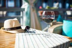 Wineglass with red wine. With hat on the table Stock Photos