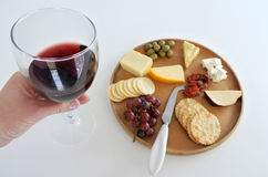 Wineglass with red wine over a cheese platter Stock Images