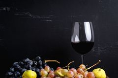 Wineglass with some red wine and ripe grapes of wine on background. Toned. Figs and grapes Copy sapce. Barrel, wineglass with some red wine and ripe grapes of Royalty Free Stock Image