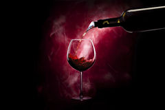 Wineglass with bottle. Wineglass with splash of wine and bottle on colored background royalty free stock image