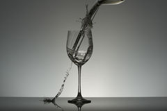 Wineglass standing on a table and water pouring from another vessel with swirl and water splashes. Stock Photography
