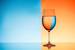 Wineglass with water over blue and orange background. Royalty Free Stock Images