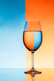 Wineglass with water over blue and orange background. Royalty Free Stock Photography