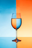 Wineglass with water over blue and orange background. Stock Photo