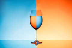 Wineglass with water over blue and orange background. Stock Image