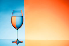 Wineglass with water over blue and orange background. Stock Photography